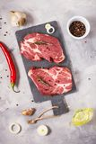 Raw meat steak with seasonings on concrete background. Steak ready for cooking. Barbecue concept. Ingredients for meat roasting. Top view Royalty Free Stock Photography