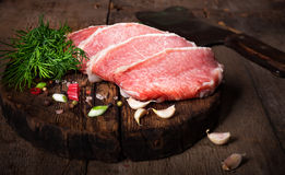 Raw meat steak with spices on a wooden board, selective focus.  Stock Image