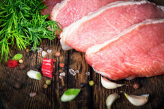 Raw meat steak with spices on a wooden board, selective focus.  Royalty Free Stock Image