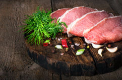 Raw meat steak with spices on a wooden board, selective focus.  Royalty Free Stock Photos