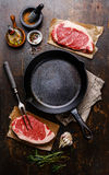 Raw meat Steak for two around iron frying pan. Raw fresh meat Steak Striploin for two with condiments around iron frying pan Stock Image