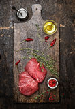 Raw meat steaks on wooden cutting board with oil, herbs and spices. Dark rustic background Royalty Free Stock Images