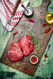 Raw meat steaks on wooden cutting board with oil, herbs and spices. Rustic background Royalty Free Stock Photo
