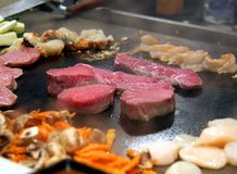 Raw meat on a stove. Scenes from a Tepanyaki style japanese cuisine performance in a restaurant Royalty Free Stock Photos