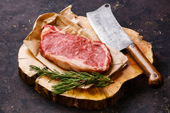 Raw meat Striploin steak and meat cleaver. Raw fresh meat Striploin steak and meat cleaver on butcher block on dark background stock photography