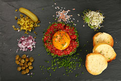 Raw meat tartare steak and egg yolk on black board Stock Photography