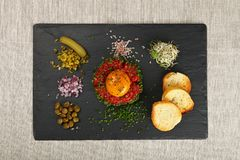 Raw meat tartare steak and egg yolk on black board. One portion of raw minced beef meat tartare steak with egg yolk, green chive, onions, cucumbers, capers, salt Stock Image