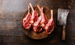 Raw meat Veal ribs on butcher block and cleaver. Raw fresh meat Veal ribs on butcher wooden block and Meat cleaver on wooden background stock image