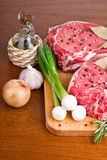 Raw meat with vegetables. Uncooked meat: raw fresh beef ready to cooking with garlic and green onions on wooden background Royalty Free Stock Photo