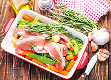 Raw meat with vegetables. In bowl and on a table Stock Photos