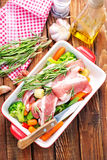 Raw meat with vegetables. In bowl and on a table Royalty Free Stock Image