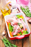 Raw meat with vegetables. In bowl and on a table Royalty Free Stock Images