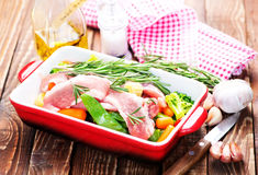 Raw meat with vegetables. In bowl and on a table Stock Images