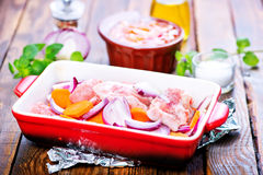 Raw meat with vegetables. In the bowl and on a table Royalty Free Stock Photos