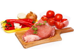 Raw meat and vegetables. On chopping board Stock Photo