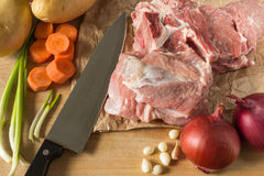 Raw meat with vegetables and greens on a wooden table surface. Royalty Free Stock Images