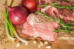 Raw meat with vegetables and greens on a wooden table surface. Stock Image