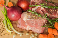 Raw meat with vegetables and greens on a wooden table surface. Stock Photography