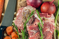 Raw meat with vegetables and greens on a wooden table surface. Royalty Free Stock Photo