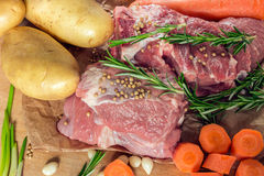 Raw meat with vegetables and greens on a wooden table surface. Preparation of dinner Stock Photography