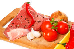 Raw meat and vegetables over the white background. Raw meat and vegetables on chopping board Royalty Free Stock Photography
