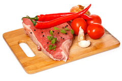 Raw meat and vegetables over the white background. Raw meat and vegetables on chopping board Royalty Free Stock Photos