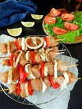 Raw meat with vegetables on skewers. Processed product for shashlik cooking Royalty Free Stock Images