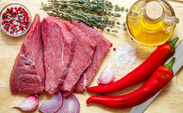 Raw meat, vegetables and spices . Fresh beef, peppers, red onion, garlic, thyme, olive oil. The ingredients for a tasty lunch Stock Images