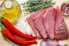 Raw meat, vegetables and spices . Fresh beef, peppers, red onion, garlic, thyme, olive oil. The ingredients for a tasty lunch Royalty Free Stock Image