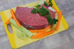 Raw meat with vegetables. On the table Stock Images