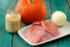 Raw meat, whole pumpkin, onion and rice with pepper mill. Closeup royalty free stock photos