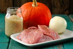Raw meat, whole pumpkin, onion and rice with pepper mill. Closeup stock photo