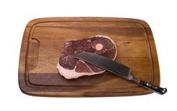Raw meat on the wooden board. Raw meat with national uzbek knife on the wooden board. Isolated on white background Royalty Free Stock Photo