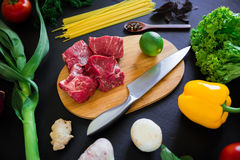 Raw meat on wooden board, knife, pasta and fresh vegetables on dark background. Top view. Flat lay. Food background. Raw meat on wooden board, knife, pasta and Stock Images