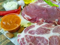 Raw meat on a wooden board pepper nuts, chili. Raw meat on a wooden board pepper butter sauce chili Stock Image