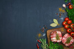 Raw meat on wooden cutting board. Decorated with vegetables and spice. Dark background. Top view Stock Photos