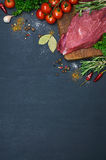 Raw meat. On wooden cutting board. Decorated with vegetables and spice. Dark background. Top view. Close-up Stock Photos