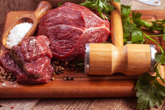 Raw meat on wooden cutting board with herbs Royalty Free Stock Photos