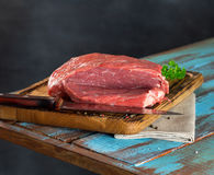 Raw meat on wooden cutting board with knife. On black background Royalty Free Stock Images