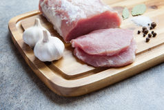 Raw meat on a wooden cutting board with spices. Raw pork on a wooden cutting board with garlic, salt, pepper, bay leaf Royalty Free Stock Photography