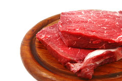 Raw meat on wooden plate. Fresh raw meat on wooden plate over white Royalty Free Stock Images