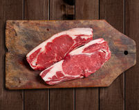 Raw meat on wooden table. Argentinean bife de chorizo raw meat on wooden table Stock Images
