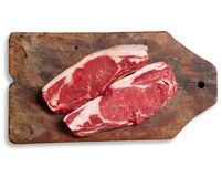 Raw meat on wooden table. Isolated, clipping path. Argentinean bife de chorizo raw meat on wooden table. Clipping path excludes shadow Royalty Free Stock Image
