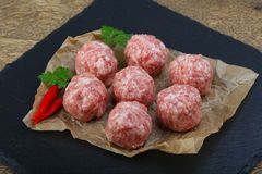 Raw meatball. With pepper and parsley on wood background royalty free stock image