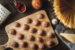 Raw meatball for spaghetti on the wooden board top view Stock Image