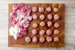Raw meatballs on the board. Chopped pork meat and chopped onions next to the meatballs Stock Photo