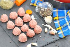 Raw meatballs on a chopping board with ingredients. Ready for cook Royalty Free Stock Photos