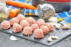 Raw meatballs on a chopping board with ingredients. Ready for cook Royalty Free Stock Photography