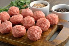 Raw meatballs on a cutting board. Close up stock photos