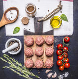 Raw meatballs on a cutting board with vegetables and herbs, oil, rosemary, garlic wooden rustic background top view close up Royalty Free Stock Image